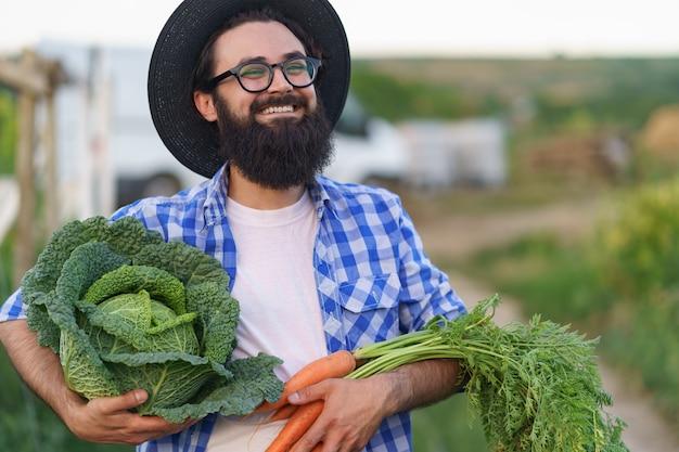 Agriculteur étreignant des légumes frais avec des mains souriantes tenant des carottes et du chou. se préparer à la livraison écologique biologique