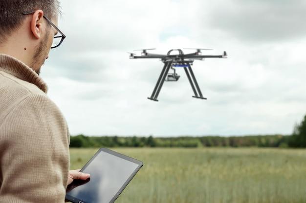 Un agriculteur gère un drone sur des terres agricoles.