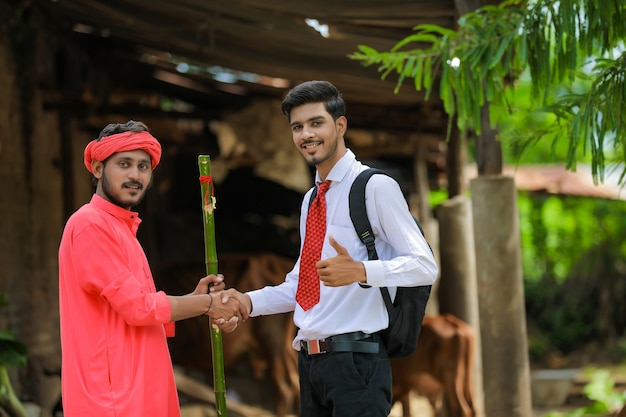 Un agriculteur indien et un banquier ou un agronome se serrent la main à la maison