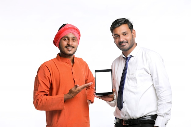 Agriculteur indien montrant une tablette avec un agent de banque ou un employé du gouvernement d'entreprise sur fond blanc.