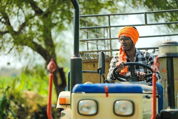Agriculteur indien avec tracteur au champ