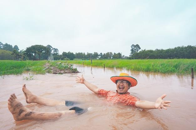 Agriculteur jouant et joyeux dans de fortes inondations dans une rizière rurale ou rurale