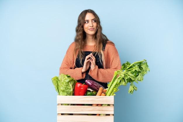 Agriculteur avec des légumes fraîchement cueillis dans une boîte complotant quelque chose