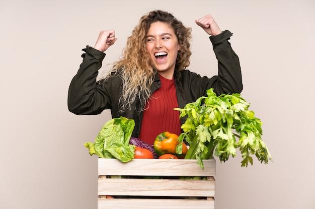 Agriculteur avec des légumes fraîchement cueillis dans une boîte isolée sur beige célébrant une victoire