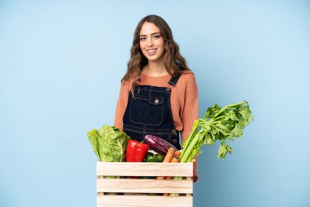 Agriculteur avec des légumes fraîchement cueillis dans une boîte en riant