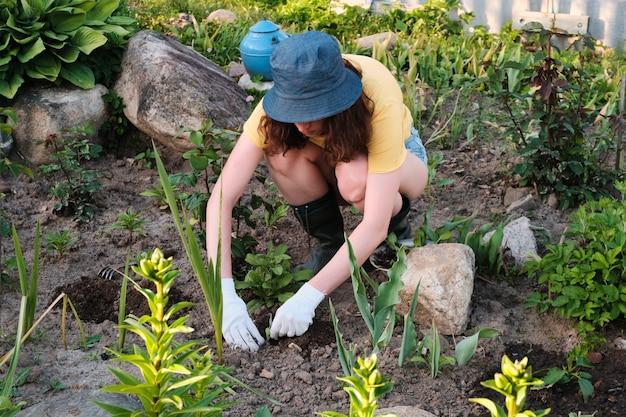 Un agriculteur plantant une plante dans le sol.