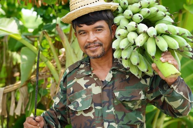 Agriculteur portant des bananes vertes
