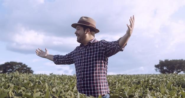 Agriculteur remerciant pour la récolte ou la pluie. plantation de soja. ferme brésilienne.
