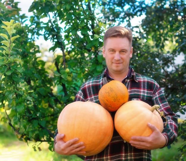 Un agriculteur se tient dans le jardin et tient une citrouille