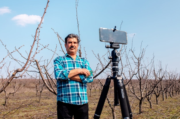 Agriculteur senior dans le verger, au printemps, enregistrant du contenu pour le vlog du blog lifestyle,