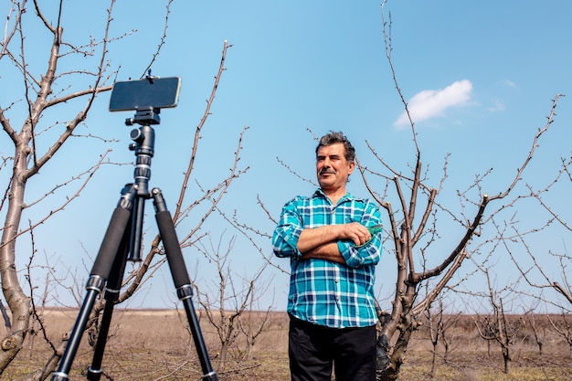 Un agriculteur senior dirige un vlog dans le verger, un agriculteur moderne utilisant les médias sociaux