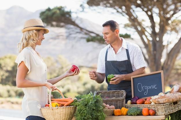 Agriculteur souriant discutant avec un client blond