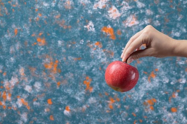 Agriculteur tenant une pomme rouge sur bleu.