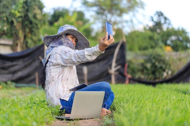 Agriculteur thaïlandais utilisant un smartphone pour prendre un selfie photo dans la ferme de légumes de la gloire du matin
