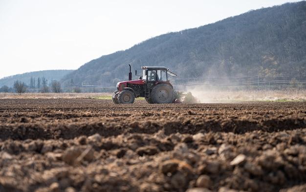 Agriculteur en tracteur préparant la terre avec cultivateur de semis au début du printemps