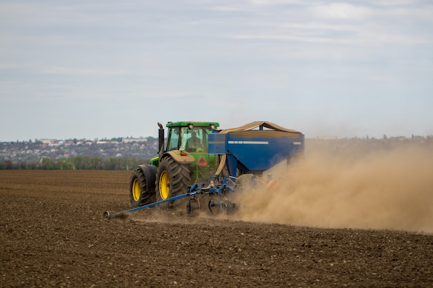 Agriculteur en tracteur préparant la terre avec un semoir dans le cadre des activités de pré-ensemencement au début de la saison des travaux agricoles sur les terres agricoles