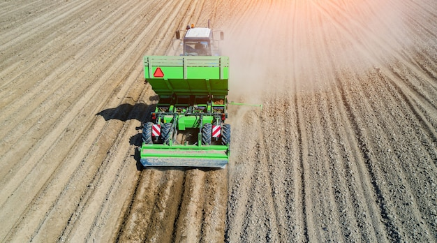 Un agriculteur et un tracteur sur le terrain plantent des pommes de terre dans les champs fertiles de la ferme. vue aérienne.