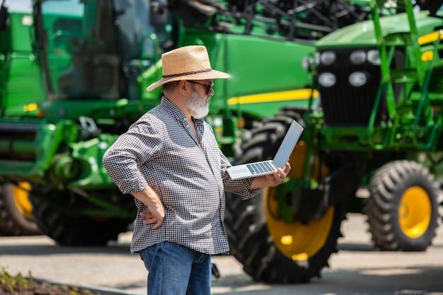 Un agriculteur avec tractos et ordinateur portable