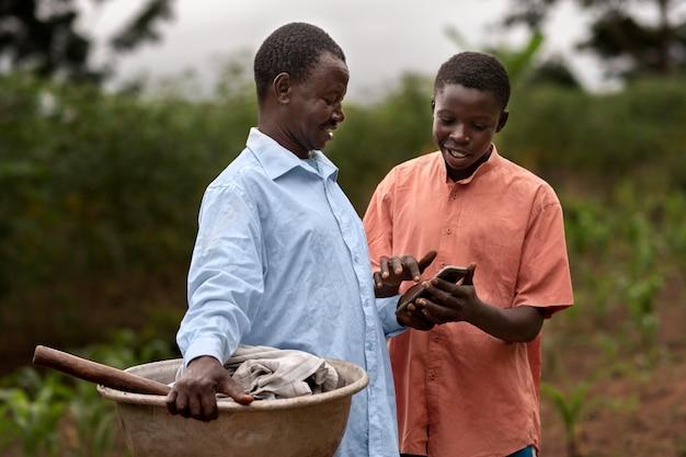 Agriculteurs de coup moyen avec smartphone