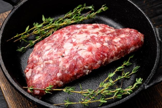 Des agriculteurs faits maison hachés crus frais font griller des hamburgers de bœuf, dans une poêle à frire en fonte, sur fond de table en bois noir