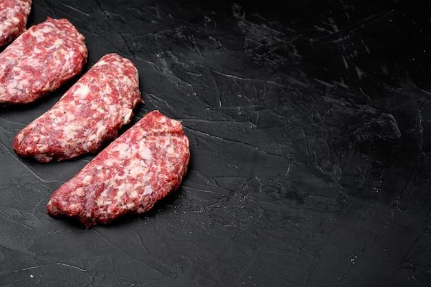 Des agriculteurs faits maison hachés crus frais font griller des hamburgers de bœuf, sur fond de table en pierre noire noire, avec espace de copie pour le texte