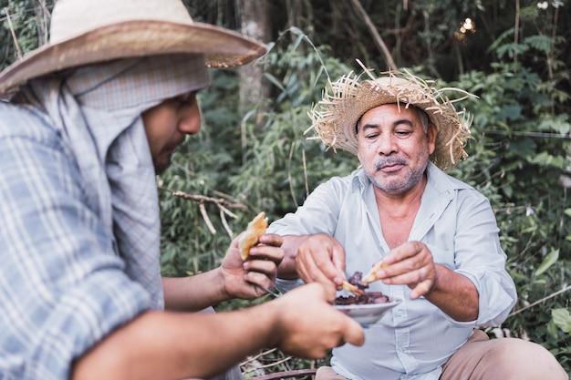 Les agriculteurs locaux mangent leur déjeuner pendant leur temps de repos.