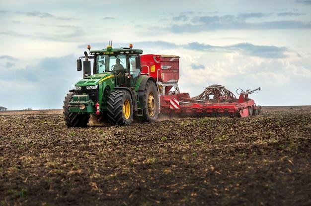 Les agriculteurs sèment et appliquent de l'engrais à l'aide d'un tracteur john deere 8370r avec un semoir pottinger terrasem c8 dans un champ labouré
