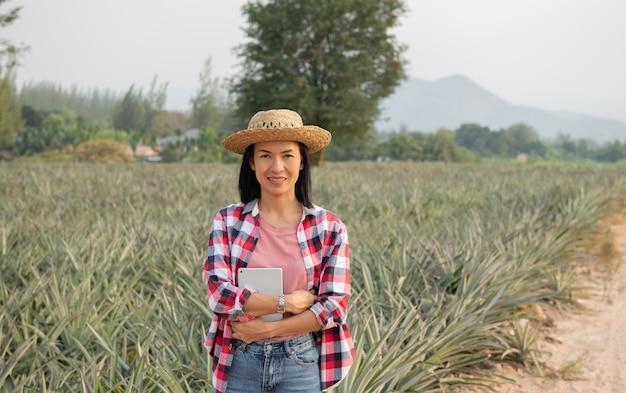Une agricultrice asiatique voit la croissance de l'ananas dans la ferme. industrie agricole, concept d'entreprise agricole.