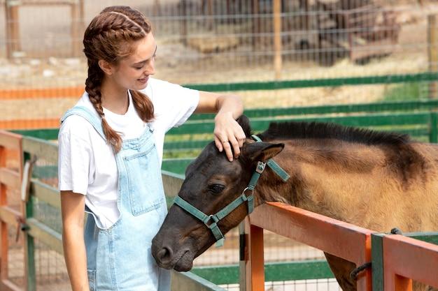 Agricultrice caressant un bébé cheval