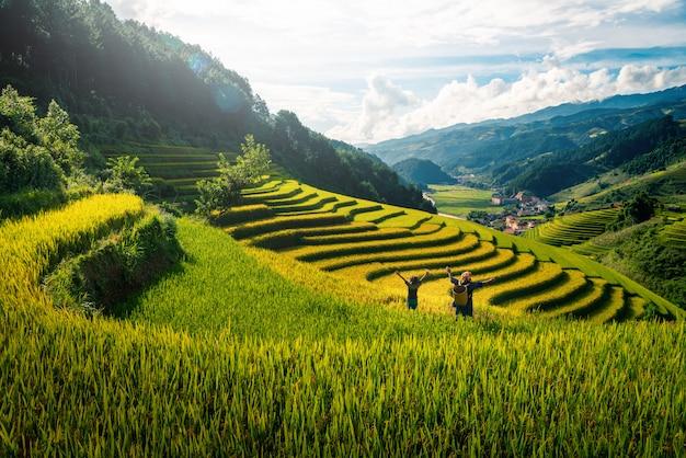 Agricultrice et fille levant le bras sur les champs de riz en terrasse au coucher du soleil au vietnam.