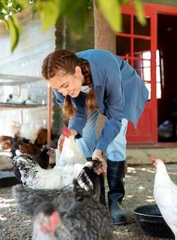 Agricultrice nourrissant les poulets