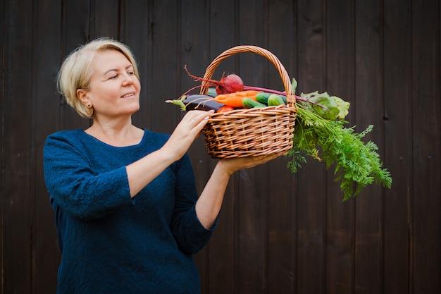 Agricultrice pensionnée tenant un panier avec des légumes biologiques cultivés dans son jardin.