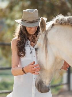 Une agricultrice plus âgée avec son cheval au ranch