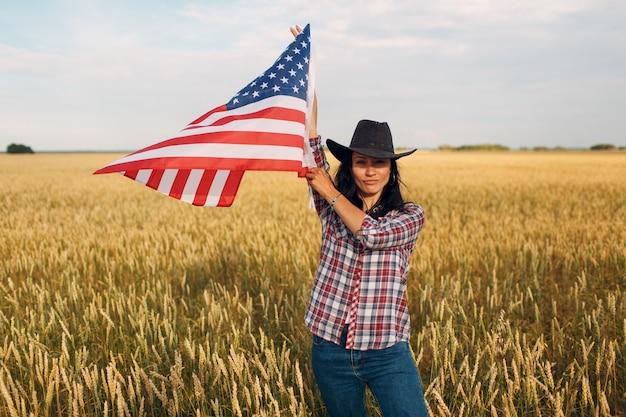 Agricultrice portant un chapeau de cowboy agitant le drapeau américain des états-unis au champ de blé