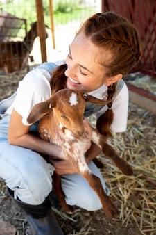 Agricultrice tenant un bébé chèvre