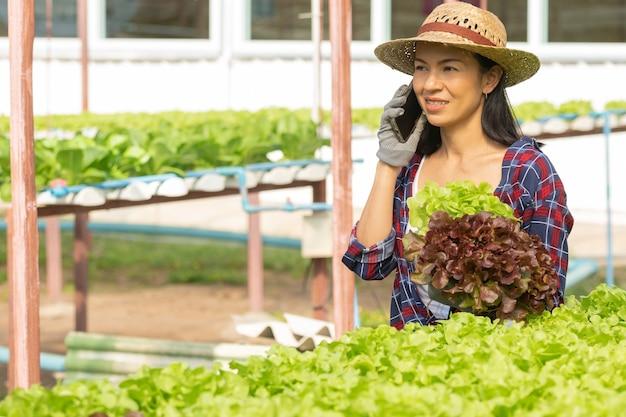 Des agricultrices asiatiques travaillant avec bonheur dans une ferme hydroponique de légumes. portrait d'une agricultrice vérifiant la qualité des légumes de la salade verte avec le sourire dans la ferme de la serre.