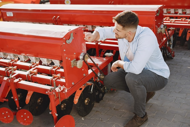 Agronome choisissant un nouveau planteur. homme au sol extérieur de la boutique. machines agricoles.