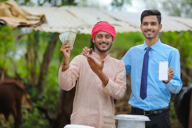 Agronome indien montrant l'écran du smartphone avec l'agriculteur