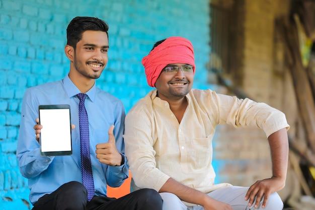 Agronome indien montrant un écran de tablette avec un agriculteur à la maison