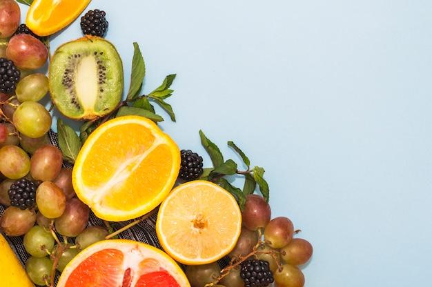 Agrumes coupés en deux; kiwi; mûres et raisins sur fond bleu
