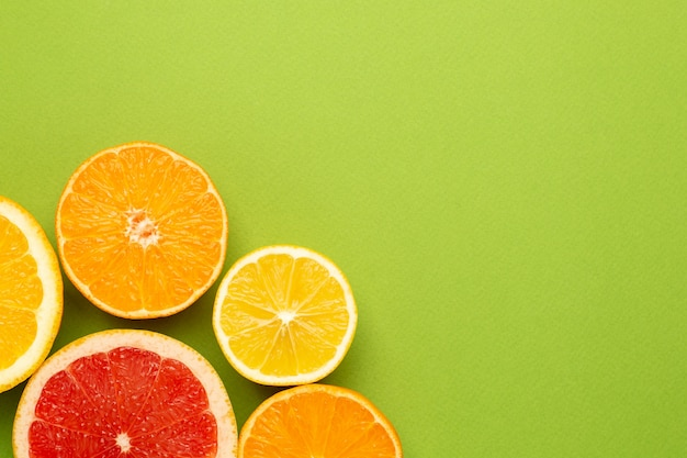 Agrumes sur fond vert avec fond, plat de fruits, composition minimale d'été avec pamplemousse, citron, mandarine et orange