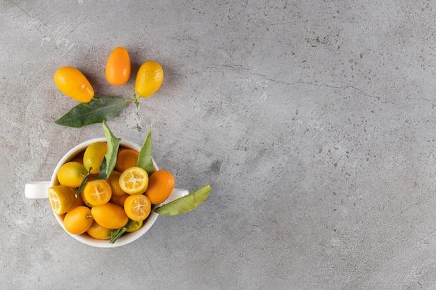 Agrumes frais cumquat entiers et tranchés avec des feuilles placées sur un bol.