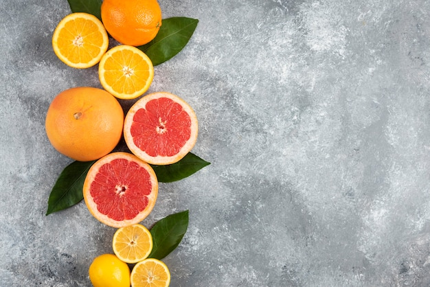 Agrumes frais, demi-coupés ou fruits entiers sur une surface grise.