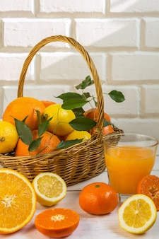 Agrumes orange citron dans un panier et jus sur un fond clair, régime alimentaire sain