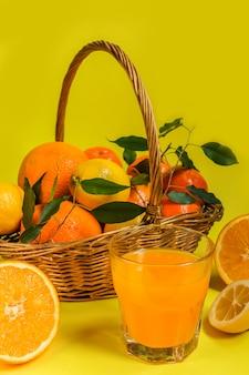Agrumes orange citron dans un panier et jus sur fond jaune, régime alimentaire sain