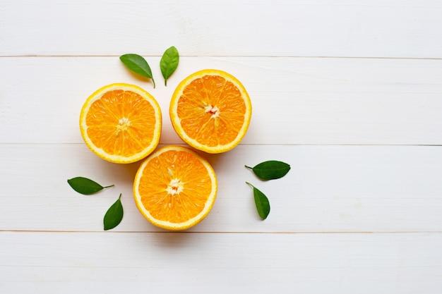 Agrumes orange frais avec des feuilles en bois blanc
