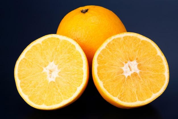 Agrumes en tranches de fruits orange sur un fond sombre