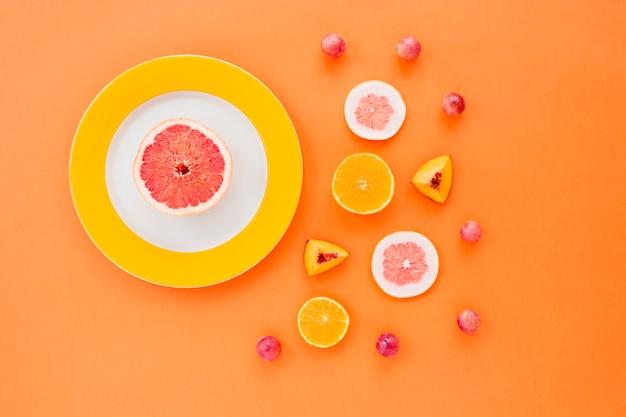 Agrumes; tranches de pêche et raisins sur fond orange