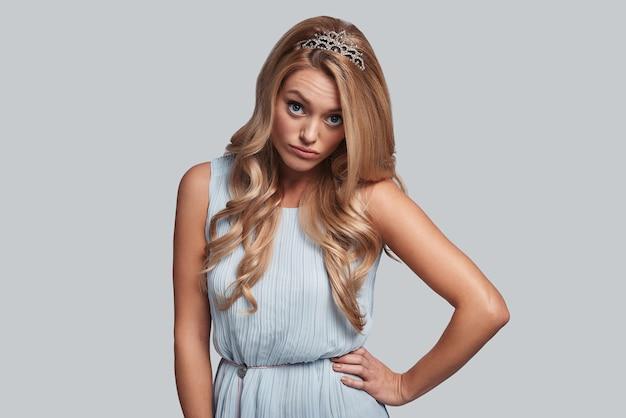 Ah bon? jolie jeune femme en couronne gardant la main sur la hanche et regardant la caméra en se tenant debout sur fond gris