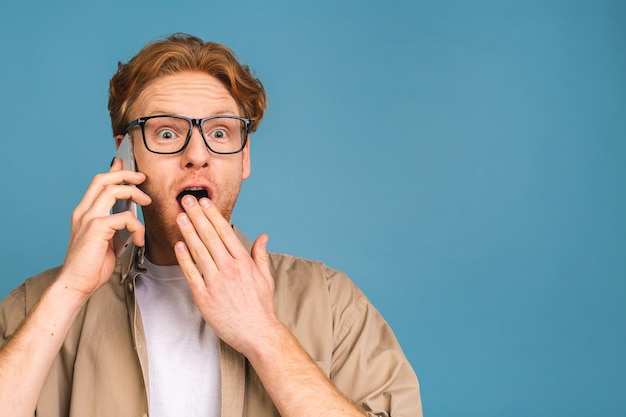 Ah bonne nouvelle ! souriant choqué étonné jeune homme décontracté parlant au téléphone mobile